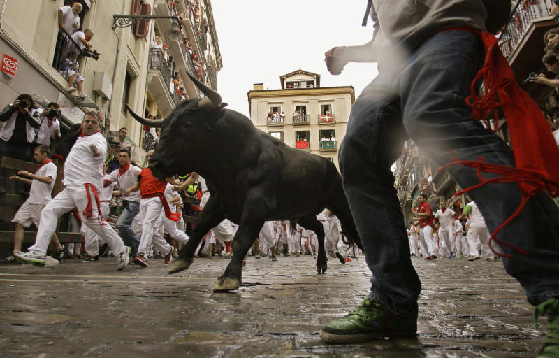 Revelers run on the Estafeta corner as a fighting bull from Miura ranch go on the way during the second running of the bulls at the San Fermin fiestas, in Pamplona northern Spain, Sunday, July 8, 2012. (AP Photo/Alvaro Barrientos)