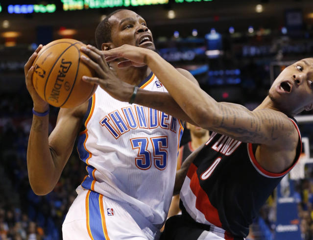Oklahoma City Thunder forward Kevin Durant (35) fouls Portland Trail Blazers guard Damian Lillard (0) as he drives to the basket in the fourth quarter of an NBA basketball game in Oklahoma City, Tuesday, Jan. 21, 2014. Oklahoma City won 105-97. (AP Photo/Sue Ogrocki)