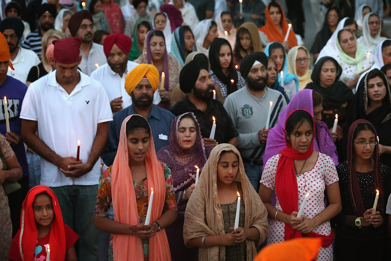 Guests attend an interdenominational candlelight vigil at the Illinois Sikh Community Center August, 6, 2012 in Wheaton, Illinois. The vigil was held to honor the victims who were killed yesterday at the Sikh Temple of Wisconsin. Wade Michael Page, a suspected white supremacist, opened fire at the temple killing six people before being killed by police.  (Photo by Scott Olson/Getty Images)