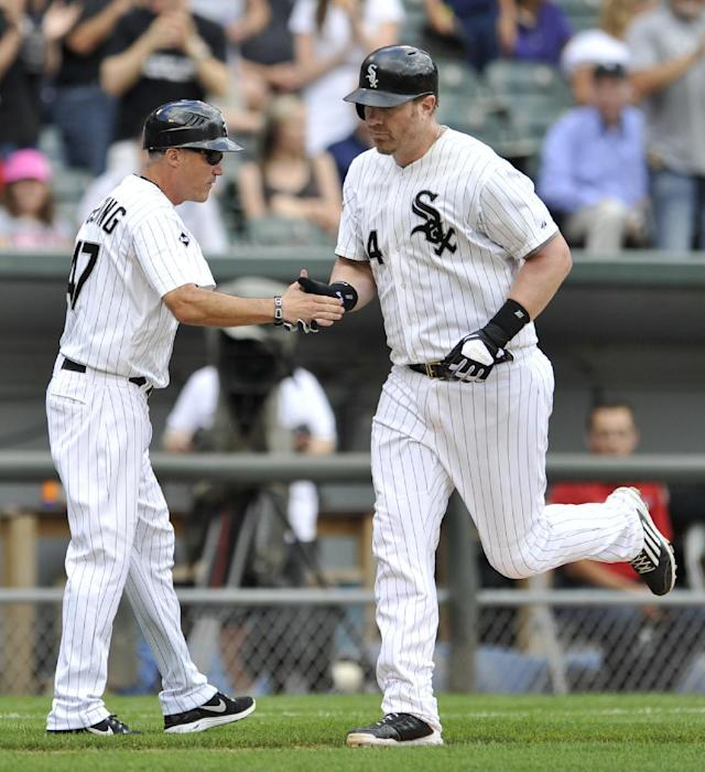 Chicago White Sox's Adam Dunn (44), celebrates with third base coach Joe McEwing (47), after Dunn hit a two-run home run during the third inning of in the first baseball game of a doubleheader against the Detroit Tigers in Chicago, Saturday, Aug. 30, 2014. Chicago won 6-3. (AP Photo/Paul Beaty)