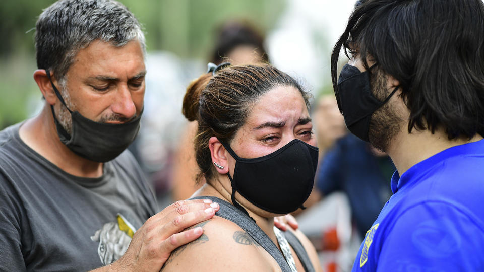 People, pictured here mourning outside the gated community where Diego Maradona lived.