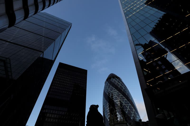 FILE PHOTO: A pedestrian walks past skyscrapers in the financial district in London