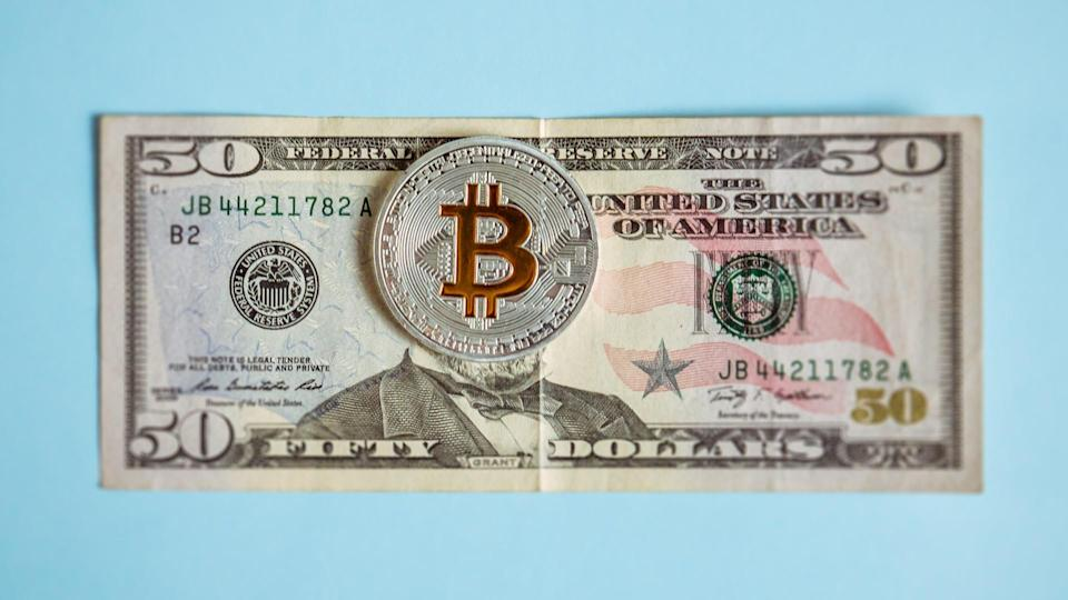Krakow, Poland, November 1, 2018, Bitcoin lies on dollars covering a portrait of the American President, the concept of the victory of cryptocurrency over paper money.