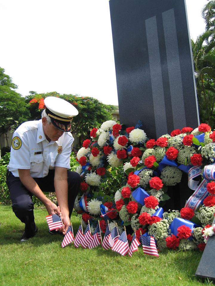 John Clark, of the Honolulu Fire Department, places a flag in front of The Eternal Flame, a memorial for the victims of the September 11th, terrorist attacks, in Honolulu, Thursday, Sept. 11, 2003. (AP Photo/Ronen Zilberman)