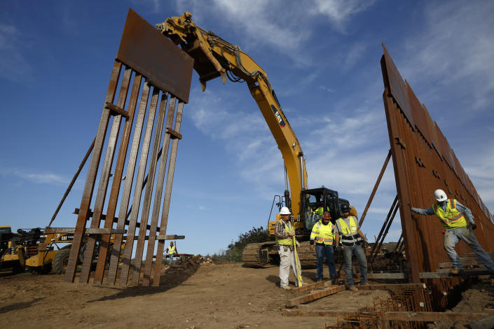 FILE - In this Jan. 9, 2019 file photo, construction crews install new border wall sections seen from Tijuana, Mexico. The government is working on replacing and adding fencing in various locations, and Trump in February declared a national emergency to get more funding for the wall. (AP Photo/Gregory Bull, File)