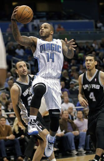 Orlando Magic's Jameer Nelson (14) goes in for a shot in front of San Antonio Spurs' Manu Ginobili, left, of Argentina, and Danny Green (4) during the first half of an NBA basketball game on Wednesday, Nov. 28, 2012, in Orlando, Fla. (AP Photo/John Raoux)