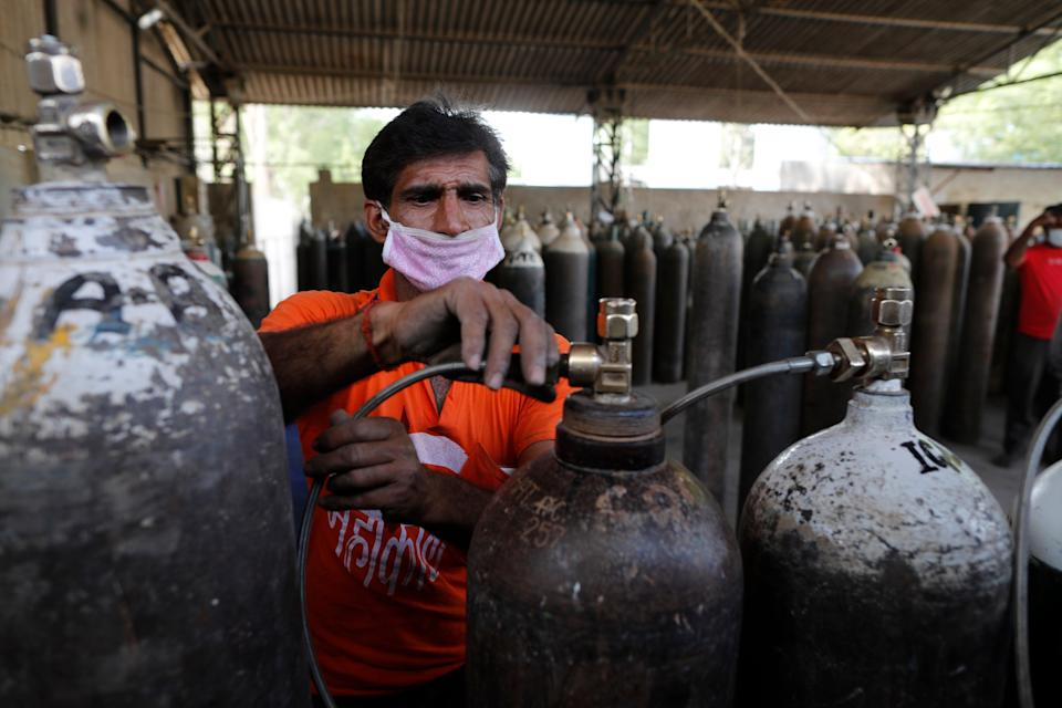 <p>A worker refills medical oxygen cylinders at a charging station on the outskirts of Prayagraj, India, on 23 April, 2021</p> (AP)