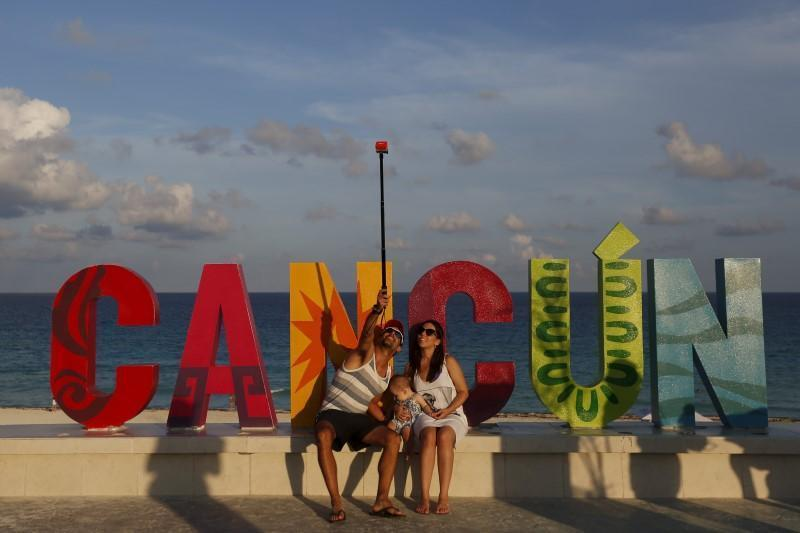 <p>Tourists pose for a selfie in Cancun on October 13, 2015 . <i>(Photo: Reuters/Edgard Garrido)</i><br></p>