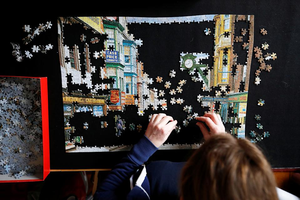 A woman does a jigsaw puzzle at her home in Manchester, England. Photo: Phil Noble/Reuters