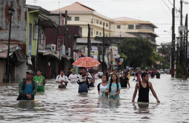 Filipino residents wade along a flooded street in Las Pinas, south of Manila, Philippines on Monday, Aug. 19, 2013. Torrential rains brought the Philippine capital to a standstill Monday, submerging some areas in waist-deep floodwaters and making streets impassable to vehicles while thousands of people across coastal and mountainous northern regions fled to emergency shelters. (AP Photo/Aaron Favila)