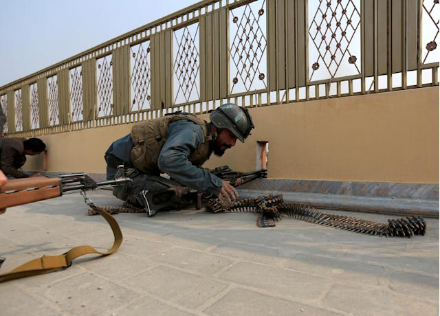 <p>An Afghan police officer takes position during a blast and gun fire in Jalalabad, Afghanistan, Jan. 24, 2018. (Photo: Parwiz/Reuters) </p>