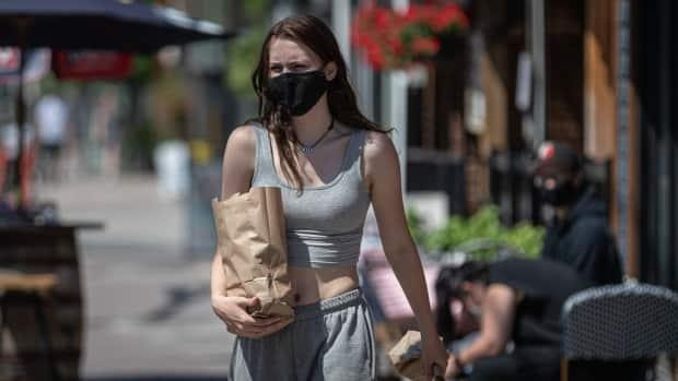 A pedestrian carries a bag while walking through downtown Ottawa on a hot day earlier this summer. Public health officials confirmed 30 new COVID-19 cases on Sunday. (Brian Morris/CBC - image credit)