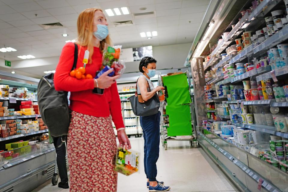 Two shoppers wearing facemasks in a supermarket in east London (Victoria Jones/PA) (PA Wire)