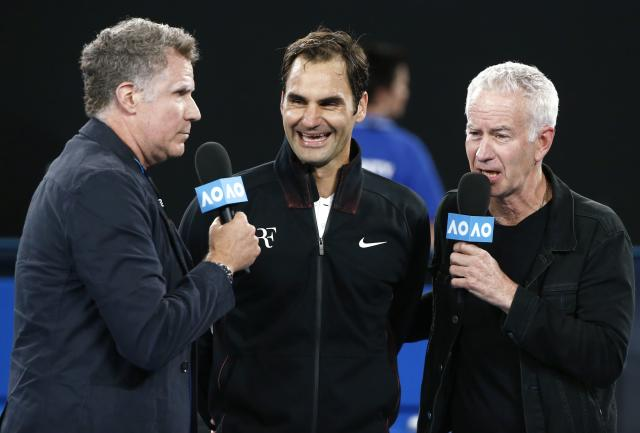 Tennis - Australian Open - Rod Laver Arena, Melbourne, Australia, January 16, 2018. Roger Federer of Switzerland speaks with actor Will Ferrell and retired tennis player John McEnroe after winning his match against Aljaz Bedene of Slovenia. REUTERS/Thomas Peter