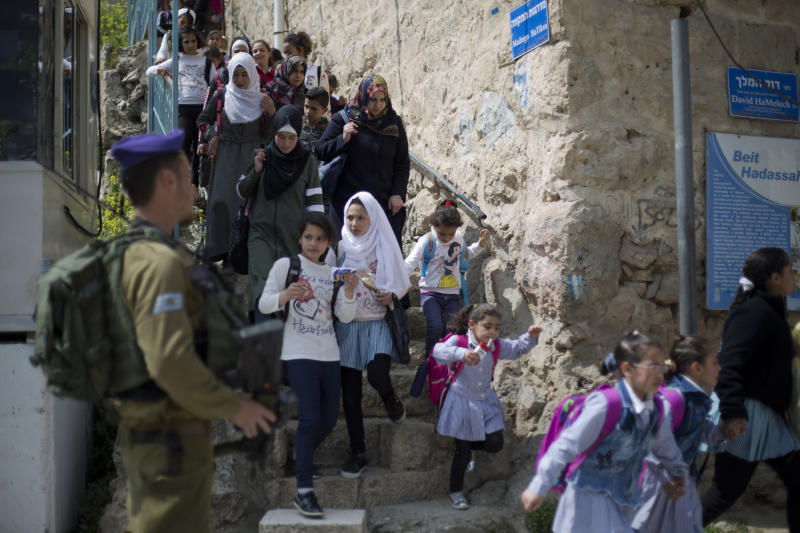 "FILE - In this March 21, 2019 file photo, an Israeli solider stands guard as Palestinian school children cross back from school in the Israeli controlled part of the West Bank city of Hebron.  Israeli Prime Minister Benjamin Netanyahu vowed Monday Sept. 16, 2019, to annex ""all the settlements"" in the West Bank, including one in Hebron, an enclave deep in the heart of the largest Palestinian city, in a last-ditch move that appeared aimed at shoring up nationalist support the day before a do-over election. (AP Photo/Ariel Schalit, File)"