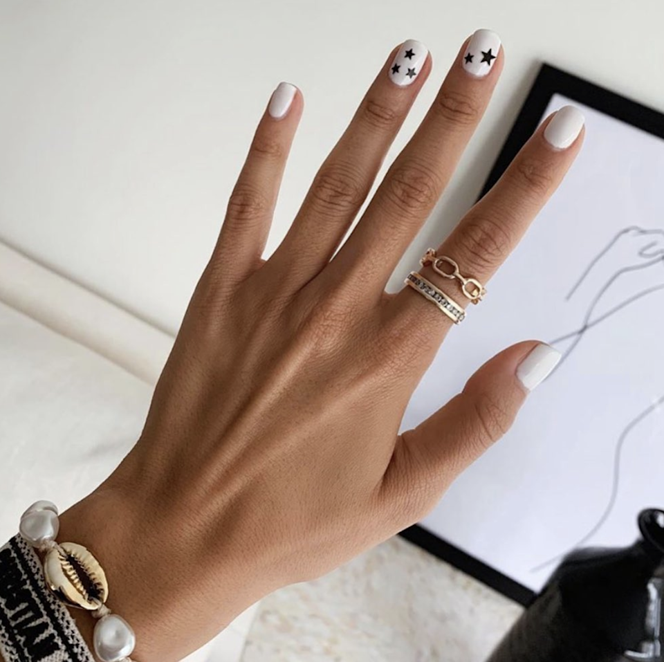 """Dainty nail art has been popular for a while at L.A.'s <a href=""""https://www.instagram.com/p/BzmA2z-Hzx2/"""" rel=""""nofollow noopener"""" target=""""_blank"""" data-ylk=""""slk:Olive & June"""" class=""""link rapid-noclick-resp"""">Olive & June</a>, and this latest iteration features tiny stars that can be applied in seconds. """"We created our <a href=""""https://olivejune.com/collections/nail-art-stickers/products/stars"""" rel=""""nofollow noopener"""" target=""""_blank"""" data-ylk=""""slk:star nail art stickers"""" class=""""link rapid-noclick-resp"""">star nail art stickers</a> after years and years of star manis in the salon,"""" says founder Sarah Gibson Tuttle. You can easily re-create the effect of sparkling constellations on a crisp base at home—she advises prepping the nail with <a href=""""https://olivejune.com/products/cuticle-serum"""" rel=""""nofollow noopener"""" target=""""_blank"""" data-ylk=""""slk:cuticle serum"""" class=""""link rapid-noclick-resp"""">cuticle serum</a> to get the cleanest effect."""