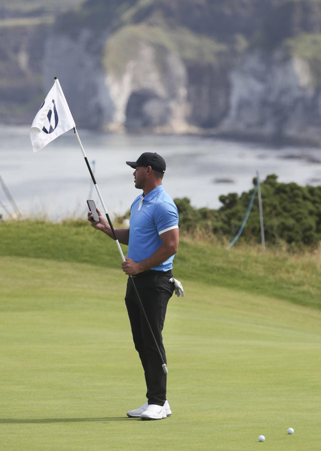 Brooks Koepka of the United States checks his smart phone as he hold the pin flag on the 5th green during a practice round ahead of the start of the British Open golf championships at Royal Portrush in Northern Ireland, Tuesday, July 16, 2019. The British Open starts Thursday. (AP Photo/Jon Super)