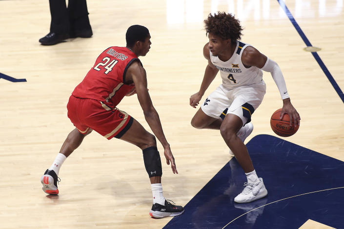 West Virginia guard Miles McBride (4) is defended by Northeastern guard Shaquille Walters (24) during the first half of an NCAA college basketball game Tuesday, Dec. 29, 2020, in Morgantown, W.Va. (AP Photo/Kathleen Batten)