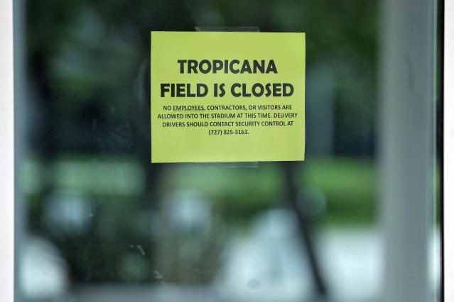 A closed sign is posted on the door at Tropicana Field, the home of the Tampa Bay Rays, Thursday, March 26, 2020, in St. Petersburg, Fla. Major League Baseball's regular season has been delayed in an attempt to help stop the spread of the coronavirus. The Rays were scheduled to open the season against the Pittsburgh Pirates. (AP Photo/Chris O'Meara)