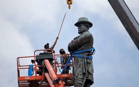 Workers in New Orleans prepare to remove a statue of General Robert Lee in May - Credit: AP