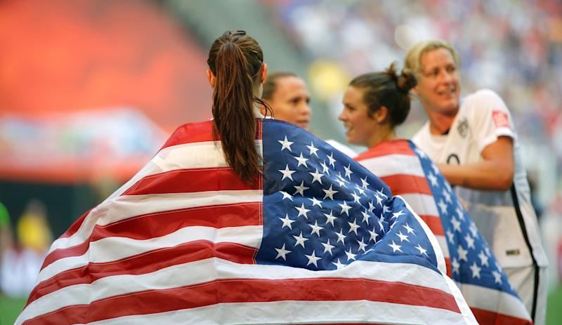 United States' Alex Morgan is draped in the U.S. flag as she celebrates with teammates after the U.S. beat Japan 5-2 in the FIFA Women's World Cup soccer championship in Vancouver, British Columbia, Canada, Sunday, July 5, 2015. (AP Photo/Elaine Thompson)