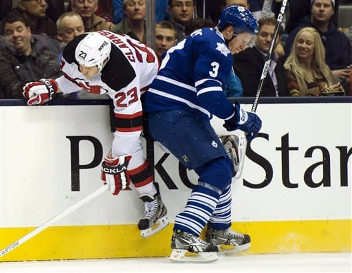 New Jersey Devils right wing David Clarkson (23) gets slammed into the boards by Toronto Maple Leafs defenseman Dion Phaneuf (3) during the first period of their NHL hockey game, Monday, March 4, 2013, in Toronto. (AP Photo/The Canadian Press, Frank Gunn)
