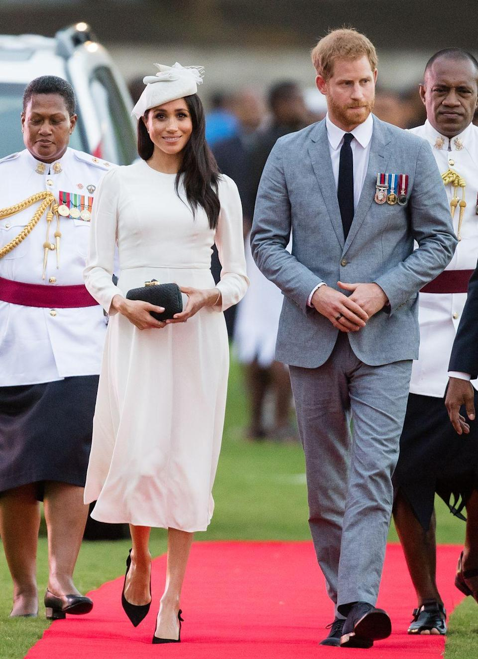 """<p>Harry and <a href=""""https://www.townandcountrymag.com/style/fashion-trends/a24066587/meghan-markle-zimmerman-royal-tour-fiji-photos/"""" rel=""""nofollow noopener"""" target=""""_blank"""" data-ylk=""""slk:Meghan have landed in Fiji!"""" class=""""link rapid-noclick-resp"""">Meghan have landed in Fiji!</a> For their arrival, the Duchess wore a white dress by <a href=""""https://www.instagram.com/zimmermann/?hl=en"""" rel=""""nofollow noopener"""" target=""""_blank"""" data-ylk=""""slk:Zimmermann"""" class=""""link rapid-noclick-resp"""">Zimmermann</a> with a matching Stephen Jones fascinator. She also wore a straw clutch by Kayu with a pair of heels by Tabitha Simmons.</p><p><a class=""""link rapid-noclick-resp"""" href=""""https://go.redirectingat.com?id=74968X1596630&url=https%3A%2F%2Fwww.bloomingdales.com%2Fshop%2Fproduct%2Ftabitha-simmons-womens-millie-slingback-pointed-toe-pumps%3FID%3D2956738&sref=https%3A%2F%2Fwww.townandcountrymag.com%2Fstyle%2Ffashion-trends%2Fg3272%2Fmeghan-markle-preppy-style%2F"""" rel=""""nofollow noopener"""" target=""""_blank"""" data-ylk=""""slk:SHOP NOW"""">SHOP NOW</a> <em>Millie Slingback Pumps by Tabitha Simmons, $695</em></p><p><a class=""""link rapid-noclick-resp"""" href=""""https://go.redirectingat.com?id=74968X1596630&url=https%3A%2F%2Fwww.shopbop.com%2Fanna-straw-clutch-kayu%2Fvp%2Fv%3D1%2F1560096446.htm&sref=https%3A%2F%2Fwww.townandcountrymag.com%2Fstyle%2Ffashion-trends%2Fg3272%2Fmeghan-markle-preppy-style%2F"""" rel=""""nofollow noopener"""" target=""""_blank"""" data-ylk=""""slk:SHOP NOW"""">SHOP NOW </a><em>Kayu Anna Straw Clutch, $157.50</em></p>"""