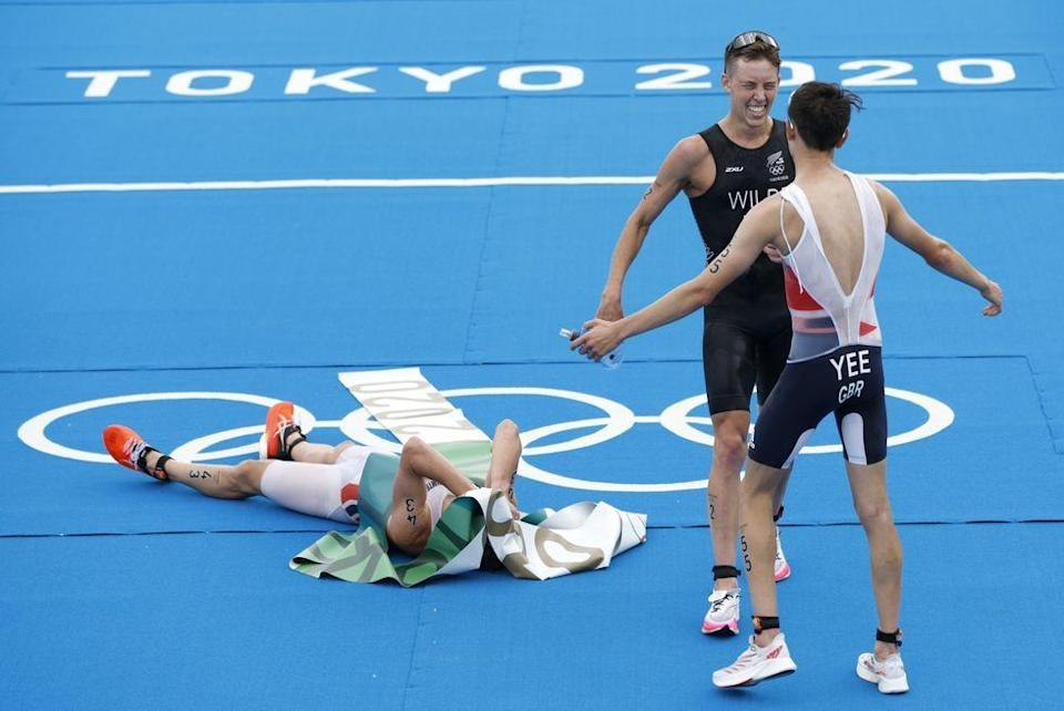<p>Kristian Blummenfelt of Team Norway lays on the ground while celebrating his gold win at the finish line, while silver winner Alex Yee of Britain and bronze winner Hayden Wilde of New Zealand celebrate off to the side during the Men's Individual Triathlon.</p>