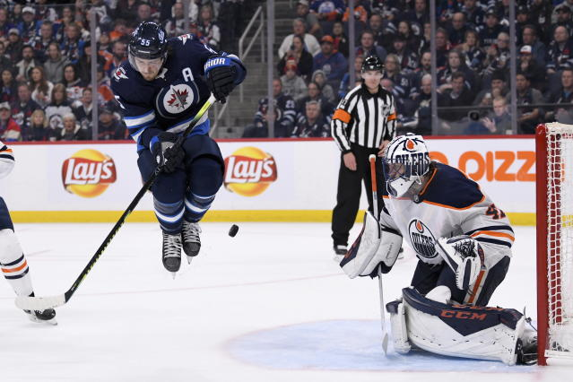 Winnipeg Jets' Mark Scheifele (55) jumps as the puck is shot toward Edmonton Oilers' Mike Smith (41) during second-period NHL hockey game action in Winnipeg, Manitoba, Sunday, Oct. 20, 2019. (Fred Greenslade/The Canadian Press via AP)