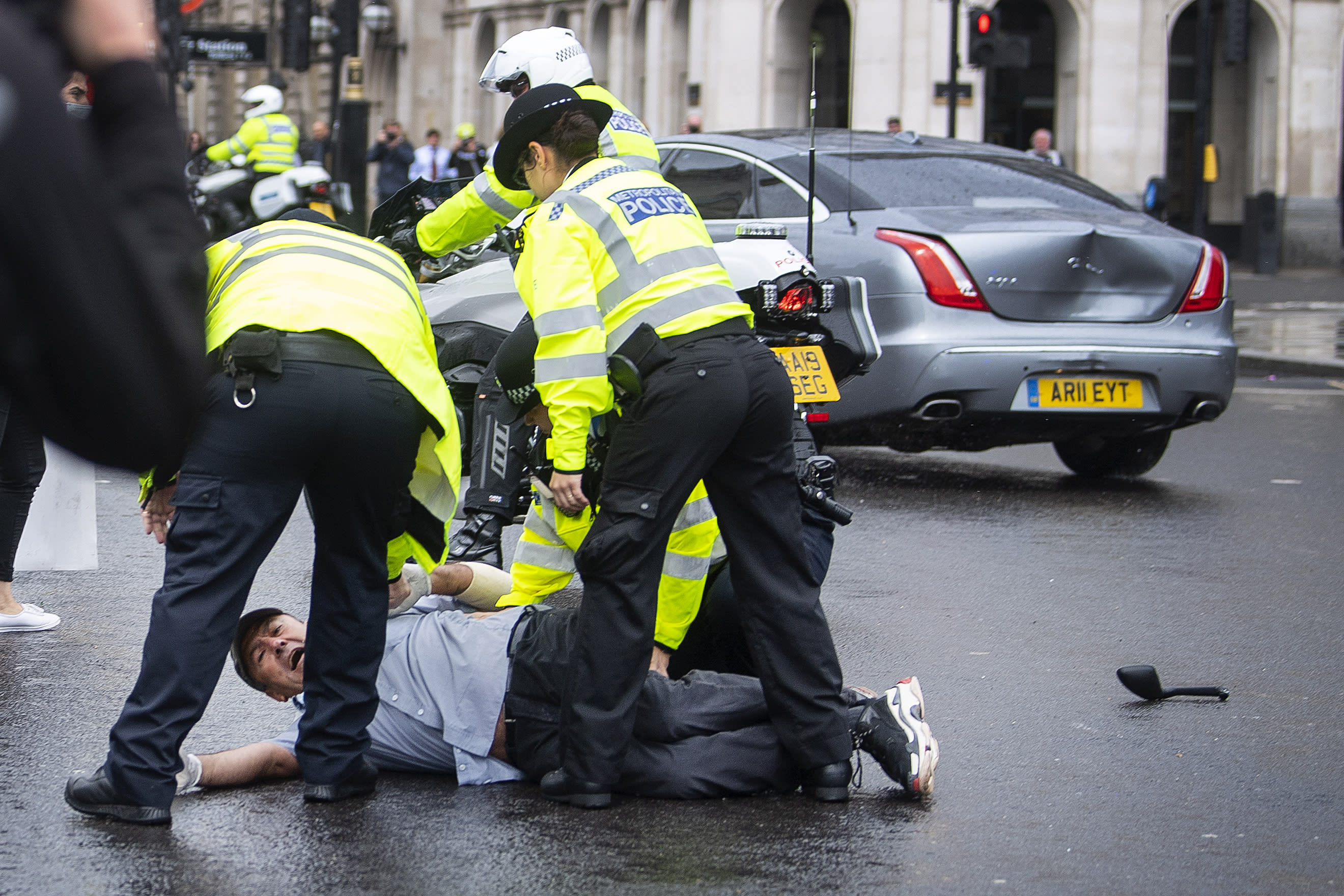 Police detain a man after he ran in front of Prime Minister Boris Johnson's car (in background with dent) as it left the Houses of Parliament, Westminster. The man, who had been demonstrating about Turkey's operation against Kurdish rebels in northern Iraq, was taken into the Palace of Westminster by officers. (Photo by Victoria Jones/PA Images via Getty Images)