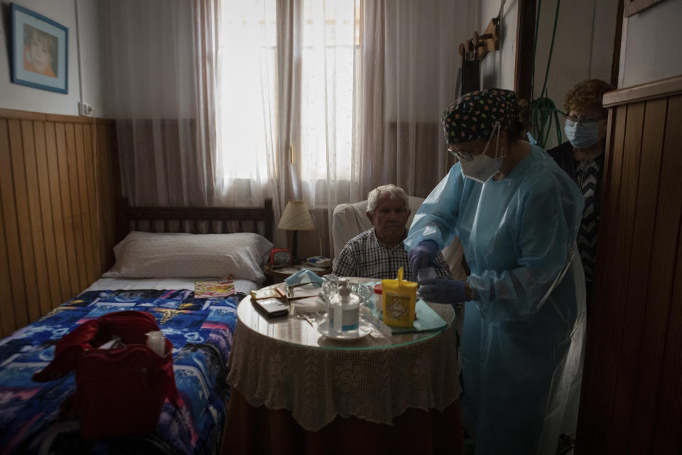 Nurse Pilar Rodríguez administers the COVID-19 vaccine to her patient Martín Gomila Serra, 82, at his home in the town of Sa Pobla on the Spanish Balearic Island of Mallorca, Spain, Friday, April 30, 2021. (AP Photo/Francisco Ubilla)