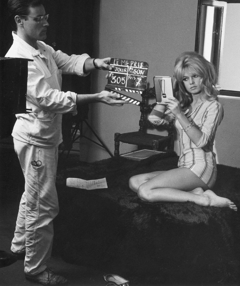<p>Iconic French actress, Brigitte Bardot, makes sure her signature blonde bouffant was just right before shooting a scene for <em>Le Mepris</em>. </p>