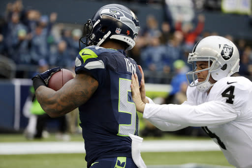Oakland Raiders quarterback Derek Carr, right, tries to tackle Seattle Seahawks outside linebacker Bruce Irvin, left, after Irvin intercepted a pass thrown by Carr and ran it for a touchdown in the first half of an NFL football game, Sunday, Nov. 2, 2014, in Seattle. (AP Photo/Elaine Thompson)