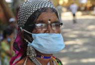 An Indian tribal woman wearing a face mask as a precaution against the coronavirus stands in front of a hospital for a general checkup in Hyderabad, India, Saturday, Dec. 5, 2020. India is second behind the U.S. in total coronavirus cases. Its recovery rate is nearing 94%. (AP Photo/Mahesh Kumar A.)
