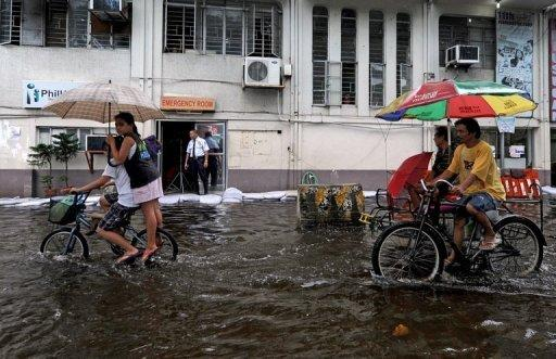 Pedicabs pedal customers down a flooded street after heavy rains in Valenzuela City, north of Manila