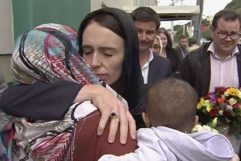 """FILE - In this Sunday, March 17, 2019 image made from video, New Zealand's Prime Minister Jacinda Ardern, center, hugs and consoles a woman as she visited Kilbirnie Mosque, in Wellington. Ardern was hailed around the world for her decisive response to the two mosque shootings by a white nationalist who killed 50 worshippers. For many Muslims, her most consequential move was immediately labeling the attack an act of terrorism. Community leaders and researchers say that for too long, terrorism was considered a """"Muslim problem"""" and that a double standard persists when attacker is white and non-Muslim. (TVNZ via AP, File)"""