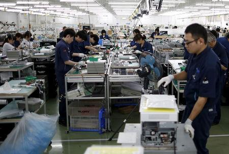 FILE PHOTO - Employees work an assembly line at a factory of Glory Ltd., a manufacturer of automatic change dispensers, in Kazo, north of Tokyo