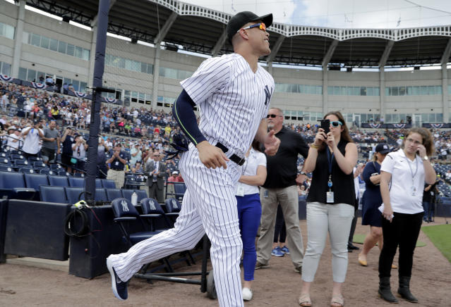 New York Yankees' Giancarlo Stanton runs from the dugout as he is introduced before a baseball spring exhibition game against the Detroit Tigers, Friday, Feb. 23, 2018, in Tampa, Fla. (AP Photo/Lynne Sladky)