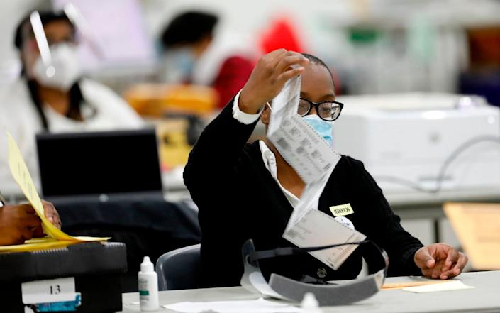 Detroit election workers work on counting absentee ballots at TCF Center - JEFF KOWALSKY/AFP