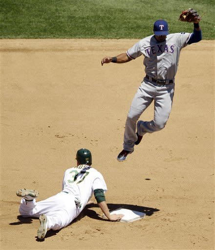 Texas Rangers shortstop Elvis Andrus, top, leaps over Oakland Athletics' Brandon Moss at second base while trying to catch an errant throw from the plate on a pickoff-attempt during the fourth inning of a baseball game on Thursday, June 7, 2012, in Oakland, Calif. (AP Photo/Marcio Jose Sanchez)