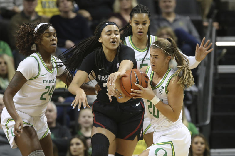 Oregon's Ruthy Hebard, left, Satou Sabally, rear, and Sabrina Ionescu, right, battle Stanford's Haley Jones for the ball during the first quarter of an NCAA college basketball game in Eugene, Ore., Thursday, Jan. 16, 2020. (AP Photo/Chris Pietsch)