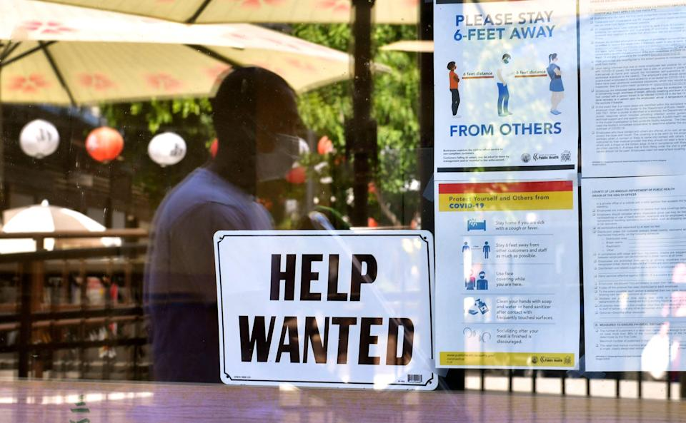"""A """"Help wanted"""" sign is posted beside coronavirus safety guidelines in front of a restaurant on May 28 in Los Angeles."""