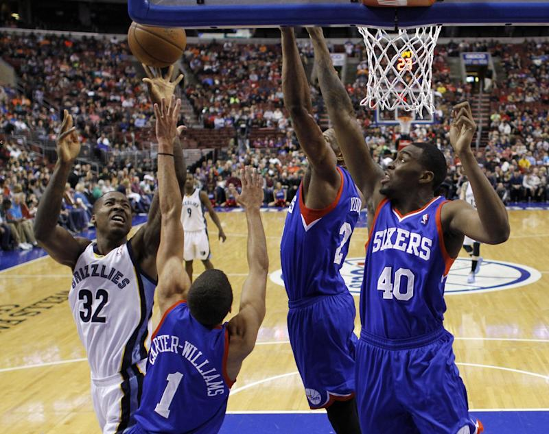 Memphis Grizzlies' Ed Davis (32) goes up for a shot against Philadelphia 76ers' Michael Carter-Williams (1), Thaddeus Young (21) and Jarvis Varnado (40) during the first half of an NBA basketball game, Saturday, March 15, 2014, in Philadelphia. (AP Photo/Matt Slocum)