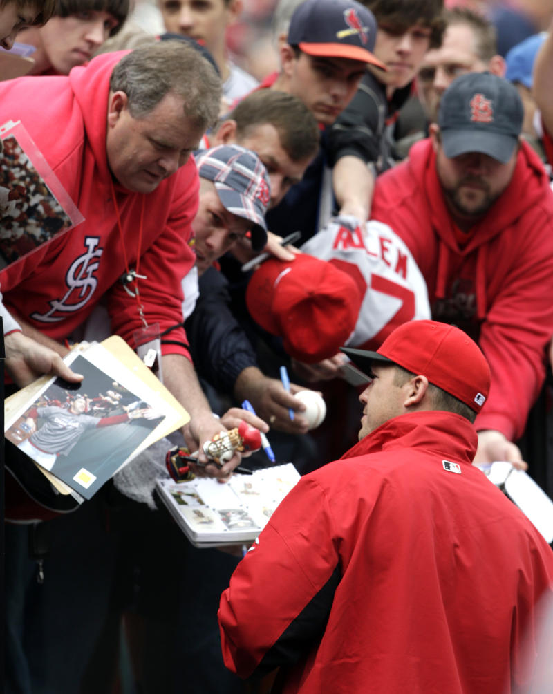 Cincinnati Reds' Scott Rolen, bottom, a former St. Louis Cardinals player, sign autographs for fans before a baseball game against Cardinals, Saturday, April 23, 2011, in St. Louis.(AP Photo/Tom Gannam)
