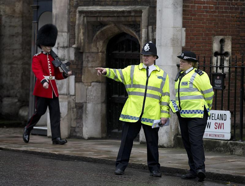 Police officers monitor the small crowd of media and royal fans outside St James's Palace, as a member of the Grenadier Guards marches past in London, Wednesday, Oct. 23, 2013. Prince William and his wife Kate have asked seven people to be godparents to their son, Prince George, who will be christened at a major royal family gathering Wednesday, palace officials said. Queen Elizabeth II and her husband Prince Philip plan to attend the christening Wednesday at the Chapel Royal at St. James's Palace, along with Prince Charles, his wife Camilla, Prince Harry and other royals. (AP Photo/Alastair Grant)