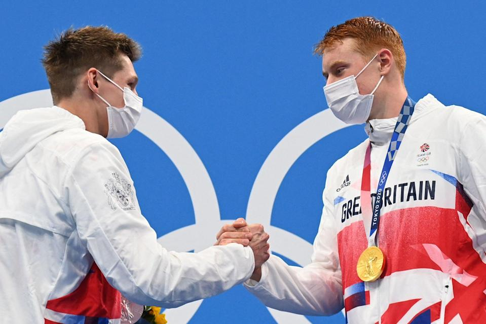 New Olympic champion Tom Dean (R) embraces roomate and silver medallist Duncan Scott on the podium in Tokyo (AFP via Getty Images)