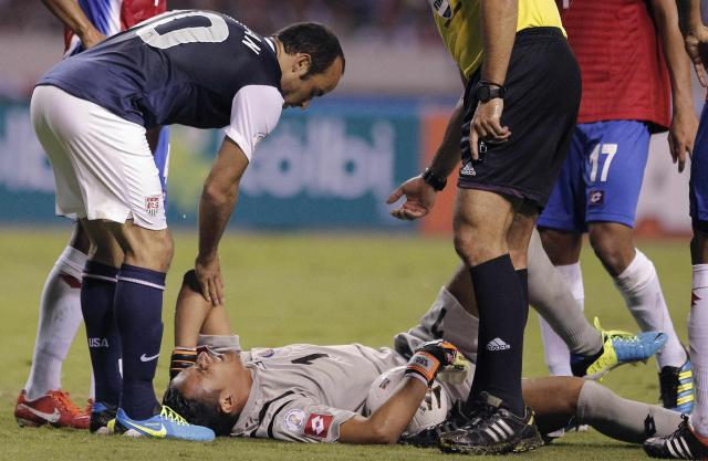 Landon Donovan (L) of the U.S. helps Costa Rica's goalkeeper Keylor Navas during their 2014 World Cup qualifying soccer match at the National Stadium in San Jose September 6, 2013. REUTERS/Juan Carlos Ulate (COSTA RICA - Tags: SPORT SOCCER)