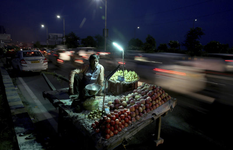 In this Thursday, Sept. 5, 2019, photo, a roadside fruit seller waits for customers as vehicles drive past in Noida on the outskirts of New Delhi, India. Confidence in the Indian economy is giving way to uncertainty as growth in the labor-intensive manufacturing sector has come to a near standstill, braking to 0.6% in the last quarter from 12.1% in the same period a year earlier. (AP Photo/Altaf Qadri)