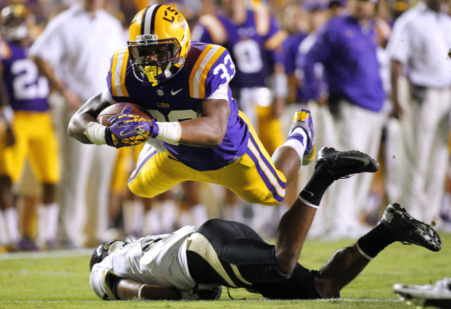 LSU Tigers running back Jeremy Hill (33) dives over Idaho Vandals cornerback Jayshawn Jordan (4) during the second half of their NCAA football game in Baton Rouge, Louisiana September 15, 2012. REUTERS/Jonathan Bachman (UNITED STATES - Tags: SPORT FOOTBALL TPX IMAGES OF THE DAY)