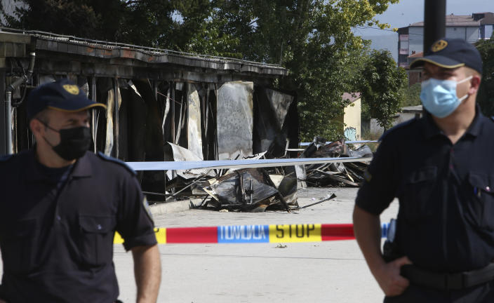 Police officers guard the access to the burned out makeshift hospital, in North Macedonia's northwestern town of Tetovo, Saturday, Sept. 11, 2021. Hundreds of people have marched Saturday in northwestern town of Tetovo to honor their 14 countrymen killed in a deadly fire that broke earlier this week and destroyed COVID-19 field hospital. (AP Photo/Boris Grdanoski)